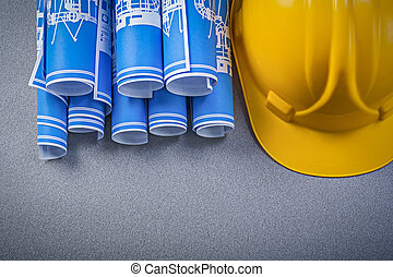 Hard hat blue rolled construction plans on grey background