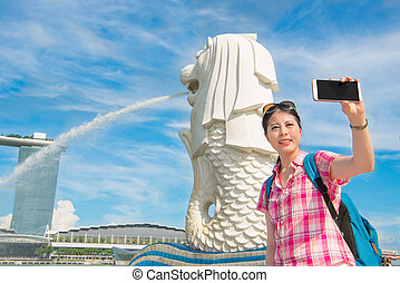 Smiling young woman making selfie near Merlion Park in...