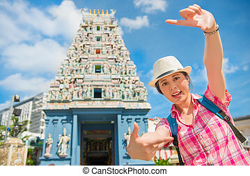 Happy young woman framing in Sri Mariamman Temple, Singapore...