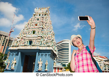 Smiling young woman making selfie near Sri Mariamman Temple,...