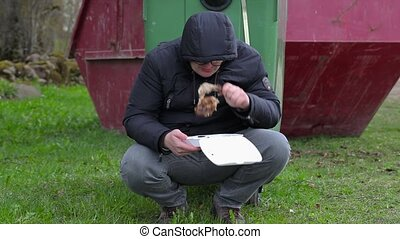 Homeless eating near waste container