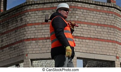 Worker with sledgehammer calling other workers near to brick...