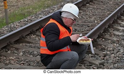 Worker sitting and eating on railway