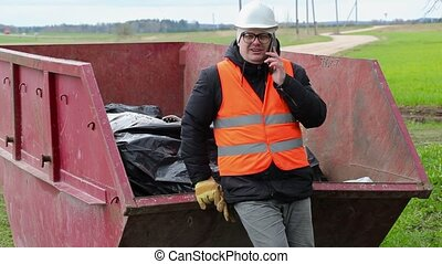 Worker talking on smart phone near waste container