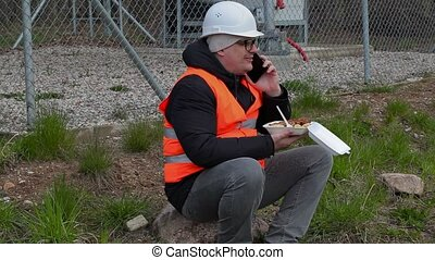 Worker sitting and talking on smart phone