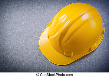 Yellow protective hard hat on grey background directly above...