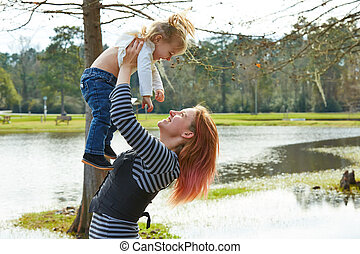 Mother playing throwing up baby girl in a lake - Mother...