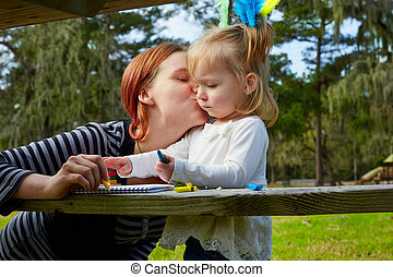Mother kissing daughter drawing colors park - Mother kissing...