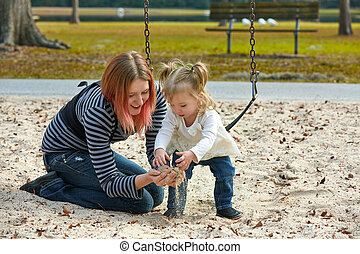 Mother and daughter playing with sand in park - Mother and...