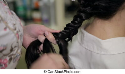 Barber making beautiful hairdo with braid - Hands of barber...