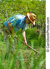 Peasant digging in the garden - Portrait of happy peasant...