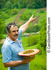 Farmer pointing to his plowing land on hill