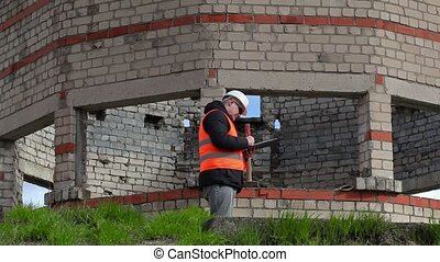 Civil engineer writing near building