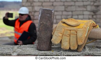 Sledgehammer and gloves on brick wall