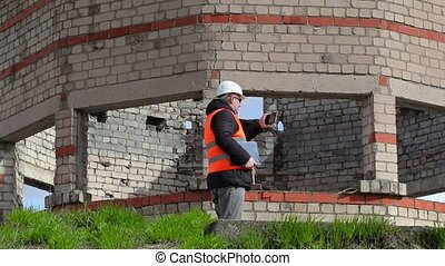 Civil engineer walking and filming on tablet PC near...