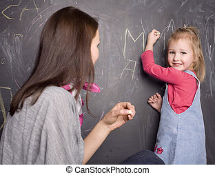 young pretty cute blond girl at blackboard in classroom with teacher