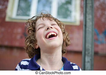 Blonde curly-haired boy cheerfully laughs