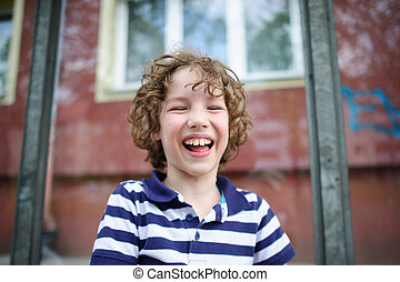 Naughty boy cheerfully laughs - 8-9 years boy laughing...