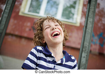 The boy in the striped shirt is filled with laughter -...