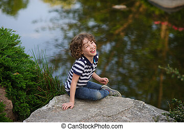 The boy sits on a large boulder near the pond - The boy with...