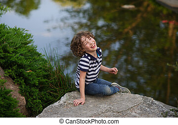 Boy laughing while sitting on a small lake - On the shore of...