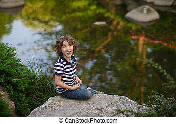 Boy sitting on a boulder in the small pond - 8-9 years boy...