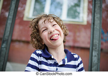 Boy laughing with his tongue out - The boy in the striped...