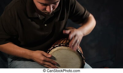 Man On Hand Drum - Young adult man drums on a traditional...