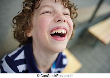 Blonde curly-haired boy laughs sincerely - Boy 8-9 years...