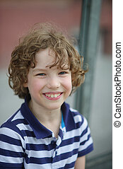 Cute little boy in a striped shirt is smiling cheerfully -...
