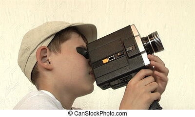 Boy shoots a film movie camera