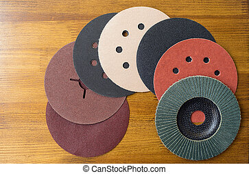 Abrasive materials - sheets of sandpaper and disks close-up...