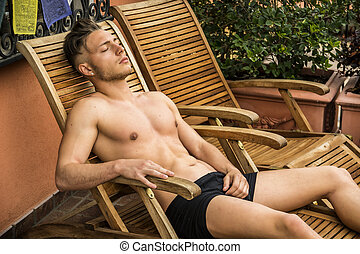 Shirtless Young Man Sunbathing in Lounge Chair