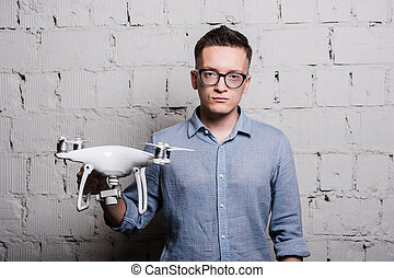 Young stylish Man in glasses holding the quadcopter drone...