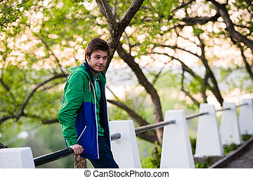 Photo of a young man using smartphone at sunset
