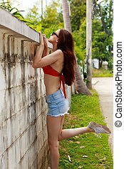 Girl in bikini and shorts near fence. - Slim skinny...