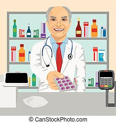 Senior male pharmacist giving pills in blister pack standing in a drugstore in front of medications on showcase