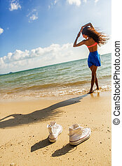 Beautiful teenage black girl in white sneakers on the sand...