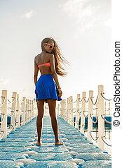 Beautiful teenage black girl in blue skirt on plastic pier....