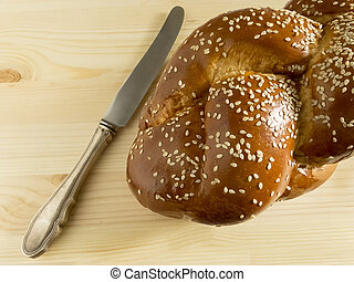 Bright Shabbat challah and knife on wooden background
