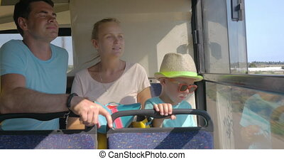 Family with child traveling by bus and looking out the...