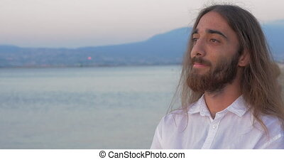 Long-haired man with beard on the beach