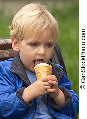 Blond boy eating ice cream outdoors
