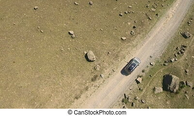 Car on a winding road in the Mountains - Aerial View Car on...