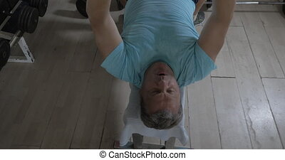 Senior man working out with weight disk - High angle shot of...