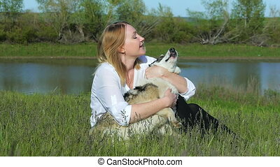 Pretty girl plays with a dog on the grass by the lake nature animals pets friend emotions happy smile dog slow motion lake sky clouds sun evening sunset girl with a dog in the sunset beach water