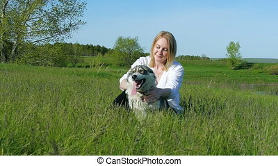 Pretty girl plays with a dog on the grass by the lake