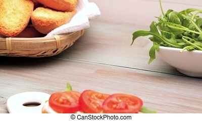 Bruschetta with cottage cheese, tomatoes and arugula served...