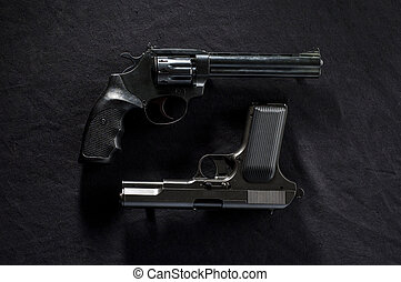 two old guns - two old revolvers on black background