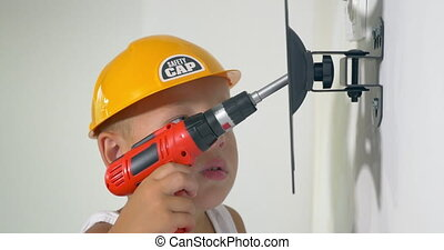 Child playing a repair at home - Little boy in yellow safety...